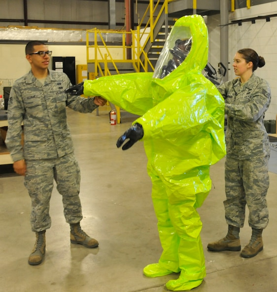 Staff Sgt. Rebecca Buhrman, 509th Civil Engineer Squadron NCO in charge of emergency management logistics, and Airman 1st Class Alfredo Guzman, 509th CES journeyman, assist Airman 1st Class Brandon Stone, 509th CES apprentice, with putting on a Level-A suit at Whiteman Air Force Base, Mo., May 22, 2013. Airmen wear this fully-encapsulated, chemical-resistant suit to enter hazardous or contaminated environments, as it is designed to prevent any air from entering or exiting. (U.S. Air Force photo by Airman 1st Class Keenan Berry/Released)