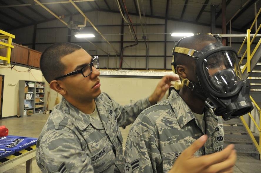 Airman 1st Class Alfredo Guzman, 509th Civil Engineer Squadron journeyman, assists Airman 1st Class Brandon Stone, 509th CES apprentice, with donning a FireHawk M7 mask at Whiteman Air Force Base, Mo., May 22, 2013. The mask is a self-contained breathing apparatus used to prevent any inhalation of chemicals or biological hazards. (U.S. Air Force photo by Airman 1st Class Keenan Berry/Released)