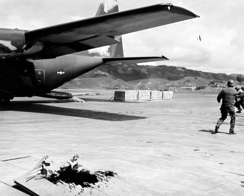 Marines rush to unload cargo from a USAF C-130 at Khe Sanh while a forward air controller (FAC) flies cover in the O-2 in the background. The FAC could quickly call in close air support to keep the enemy from firing mortar rounds at the C-130. Note the hole left in the ramp by a mortar. (U.S. Air Force photo)