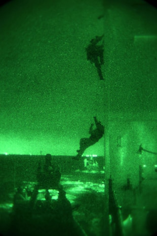 Members of 1st Marine Special Operations Battalion practice boarding and takedown of a ship at night. Marines train for Visit, Board, Search and Seizure (VBSS) at the highest level. This type of interdiction involves a non-compliant ship, underway, opposed, and at night. The operators have to attach a grappling ladder to the superstructure to board vessels with high entry points.