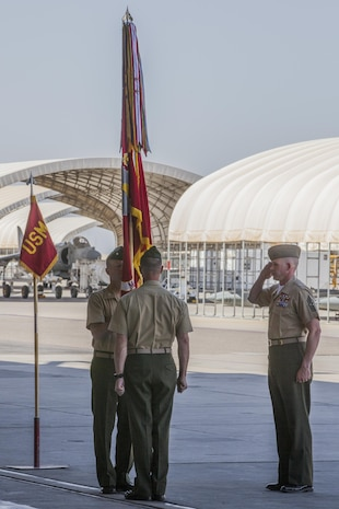 Lt. Col. Troy Pehrson, the outgoing commander of Marine Attack Squadron 211, center, passes the Marine Corps Colors to Lt. Col. Cory Simmons, the incoming commander of VMA-211, left, as Sgt. Maj. Michael Cayer, the sergeant major of VMA-211, right, salutes this symbolic act of the changing of command at the squadron hangar on Marine Corps Air Station Yuma, Ariz., May 31. Lt. Col. Pehrson's next command will be at MCAS Cherry Point, N.C.