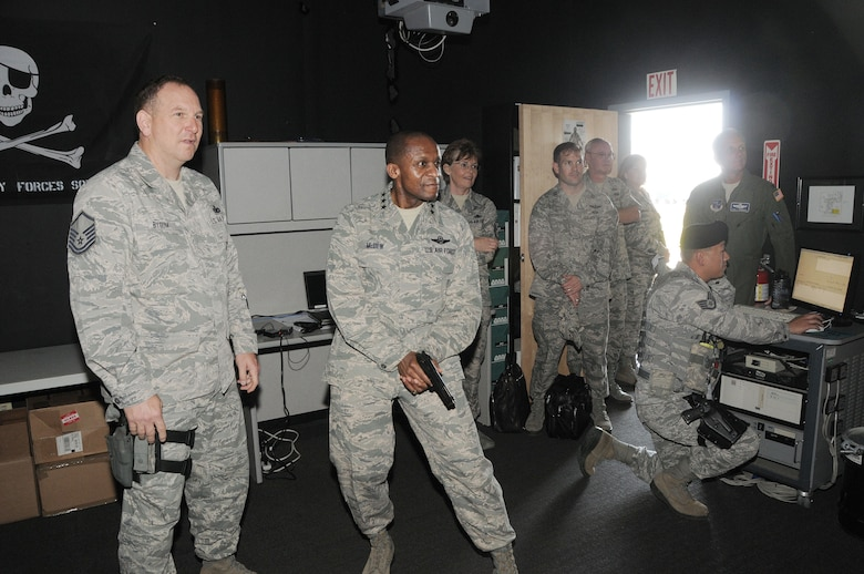 Lt. Gen. Darren McDew commander of the 18th Air Force is briefed by Master Sgt. Duane Bygum of the 146th Security Forces, California Air National Guard prior to participating in a training scenario on the Wing?s Firearms Training Simulator (FATS) on May 11, 2013. McDew?s visit was part of an overall familiarization tour of the missions and facilities at the 146th Airlift Wing, Port Hueneme, Ca.  Air National Guard photo by Master Sgt. Dave Buttner