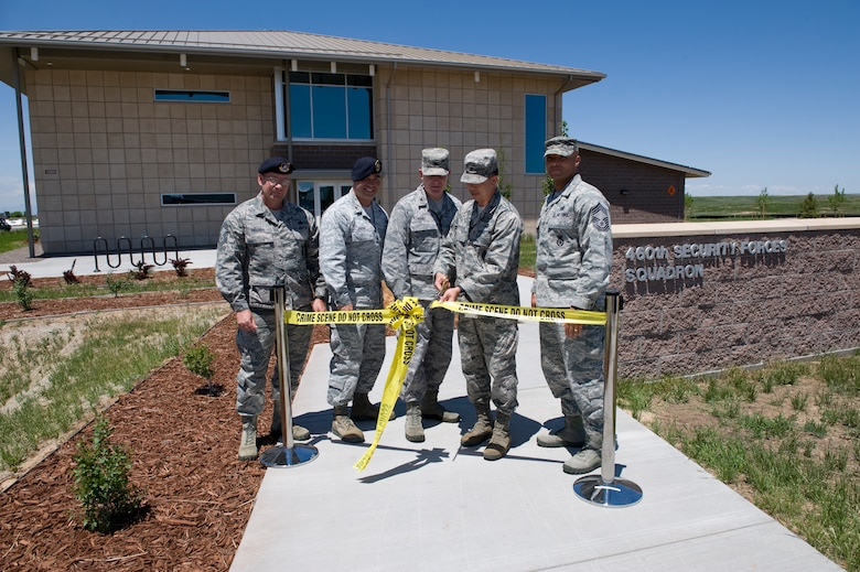 Leadership from the 460th Space Wing and 460th Mission Support Group cut the ribbon during the ribbon-cutting ceremony for the new 460th Security Forces Squadron building June 6, 2013, on Buckley Air Force Base. Thebuilding was designed to be Leader in Energy and Environmental Design certified. It includes using natural lighting and a heat pump that can be used year round to both heat and cool the building. (U.S. Air Force photo by Senior Airman Phillip Houk/Released)