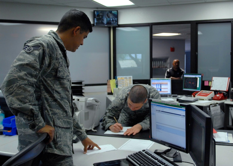U.S. Air Force Senior Airman Ralph Ruiz and Airman 1st Class Chris Greg, both from the 355th Operations Support Squadron base operations, complete paperwork after coordinating with other agencies, such as 355th Fighter Wing Command Post, on runway activities at Davis-Monthan Air Force Base, Ariz., June 4, 2013. One of the primary duties of Airmen assigned to base ops is to track inbound and outbound aircraft. (U.S. Air Force photo by Airman 1st Class Saphfire Cook/Released)