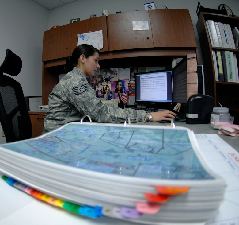 U.S. Air Force Staff Sgt. Amanda Villarreal, 355th Operations Support Squadron noncommissioned-officer-in-charge of wing scheduling, reserves air space for installation aircraft at Davis-Monthan Air Force Base, Ariz., June 4, 2013. The map sitting on her desk illustrates the airspace by sections, allowing her to quickly and easily schedule airspace over areas such as Tombstone, Ariz. (U.S. Air Force photo by Airman 1st Class Saphfire Cook/Released)
