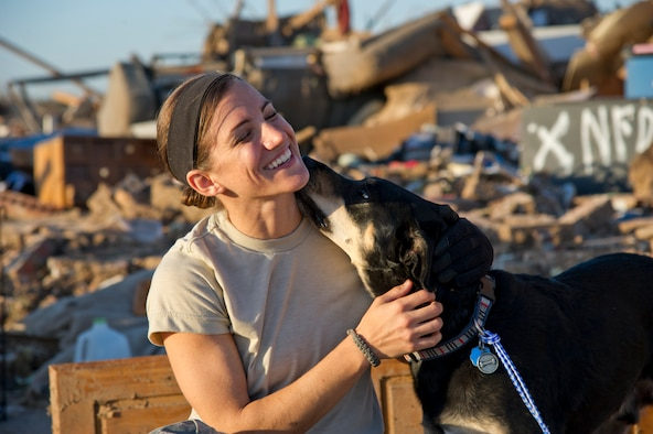 U.S. Air Force Staff Sgt. Caroline Hayworth, 4th Combat Camera Squadron, receives a friendly lick from a thankful dog expressing his excitement after pulling him from the remains of a home three days after a tornado completely destroyed his owners house, Okla., May 22, 2013. The 2 mile wide tornado demolished hundreds of houses and took lives, May 20, 2013. (Photo by Mike Meinhardt/Released)
