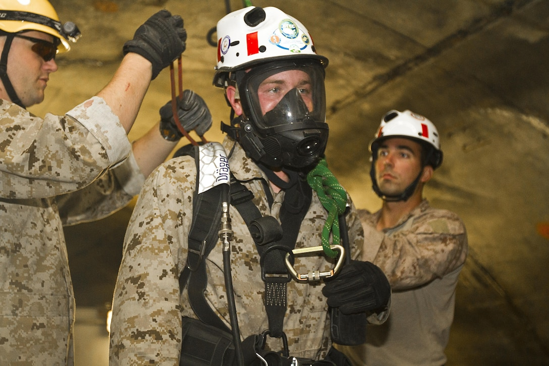 Lance Cpl. Dakota Robinson, 22nd Marine Expeditionary Unit chemical, biological, radiological and nuclear defense specialist and native of Springtown, Texas, prepares to be lowered into the confined-space trainer to search for a casualty at the Center for National Response in Gallagher, W.V., May 30, 2013. A group of 10 Marines and a corpsman from the 22nd MEU completed the 10-day course, which also covered rope rescues and rescue tactics in collapsed structures, May 30 in preparation for the unit's deployment early next year. (Marine Corps photo by Lance Cpl. Krista James/released)
