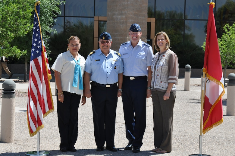Air General Jaime Figueroa, Commanding General, Peruvian Air Force and his wife, Cecilia, and Lt. Gen. Robin Rand, 12th Air Force (Air Forces Southern) commander, and his wife, Kim, stand next to their respective countries' flags in front of the 12th Air Force headquarters building here, June 10. The Peruvian Air delegation is at D-M for discussions relating to building partnership capacity, countering transnational organized crime, and humanitarian assistance and disaster response in the U.S. Southern Command area of responsibility (USAF photo by Master Sgt. Kelly Ogden/Released).