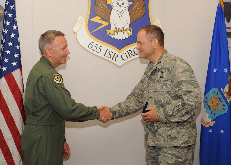 Col. Douglas Drakeley, 655th ISR Group commander, presents Maj. Gen. Bill Binger, 10th Air Force commander, with the first 655th ISR Group coin. The general was here recently and toured the group giving members coins and even a set of well-deserved Master Sgt. stripes. (U.S. Air Force photo/Staff Sgt. Veronica A. Pierce)