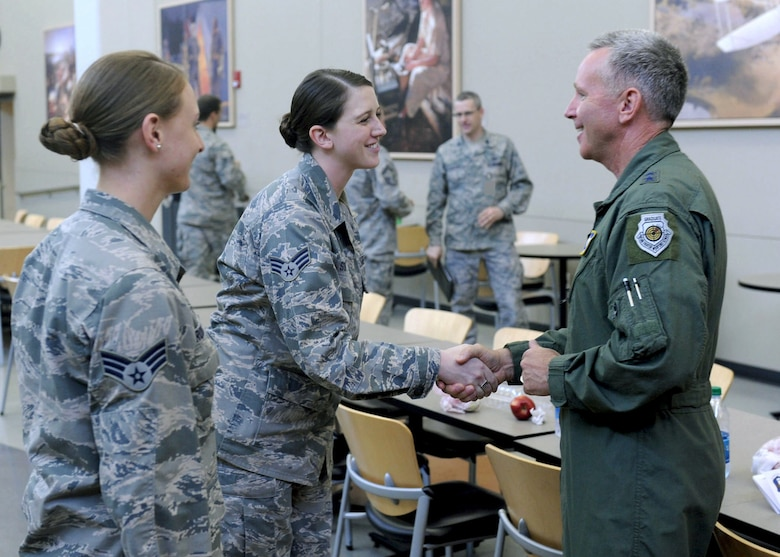 Maj. Gen. Bill Binger, 10th Air Force commander, shakes hands with Senior Airman Laura Soper, 71st IS, during his recent visit to the group as Senior Airman Leslie Brown, 71st IS, stands listens in to her left. (U.S. Air Force photo/ Staff Sgt. Michael J. Veloz)