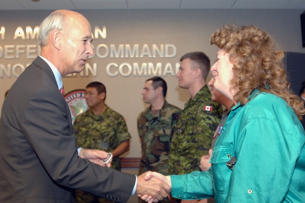 The Honorable G. Kim Wincup, chairman of the Reserve Forces Policy Board, recognizes Kim Robinson of U.S. Northern Command with his coin during the Board's visit to North American Aerospace Defense Command and USNORTHCOM headquarters at Peterson Air Force Base, Colo., on April 16, 2008. Members of the Reserve Forces Policy Board, the principal policy advisor on reserve matters to the secretary of defense, came to the commands to more learn about NORAD's and USNORTHCOM's homeland defense and civil support missions.