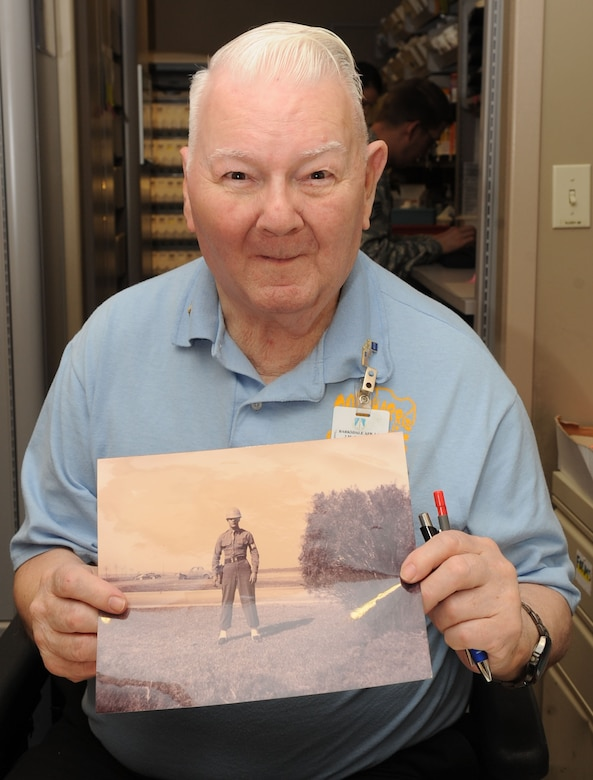Dock Harris, 2nd Medical Group pharmacy volunteer, poses with a photo of himself in the Army Air Corps in 1949 on Barksdale Air Force Base, La., June 11, 2013. Harris served 13 years in the military before he was injured in Korea in 1951. He has volunteered for the pharmacy for the past 32 years. (U.S. Air Force photo/Senior Airman Kristin High)