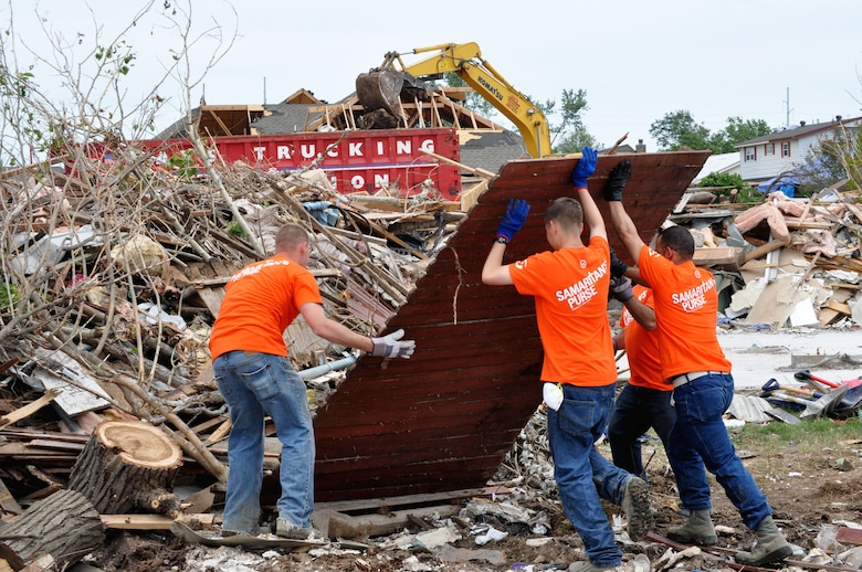 June 8, several airmen work hard to lift debris onto the ever growing pile caused by the destructive winds of the EF-5 (Enhanced Fujita Scale) tornado that tore through Moore, Okla. May 20. Over 1,150 homes were destroyed by the tornado. (U.S. Air Force photo/Kimberly Goff /Released)