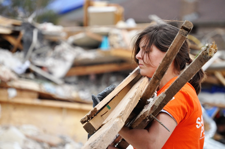 Airman Basic Brittany Orellana, 363rd Training Squadron, Sheppard Air Force Base, Texas, carries debris June 8, 2013, from the ravaged houses caused by the EF-5 (Enhanced Fujita Scale) tornado that violently blew through Moore, Okla. May 20 towards the ever growing pile. More than 100 people were rescued from the rubble caused by the twister May 20. (U.S. Air Force photo/Kimberly Goff /Released)