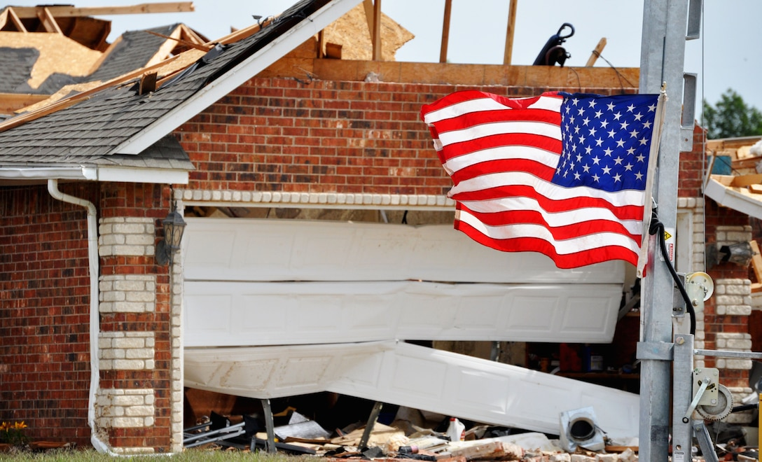 An American flag flies proudly despite the carnage that lies behind it. A house destroyed by the EF-5 (Enhanced Fujita Scale) tornado that tore through Moore, Okla. May 20.The tornado caused more than $2 billion in damages. (U.S. Air Force photo/Kimberly Goff /Released)