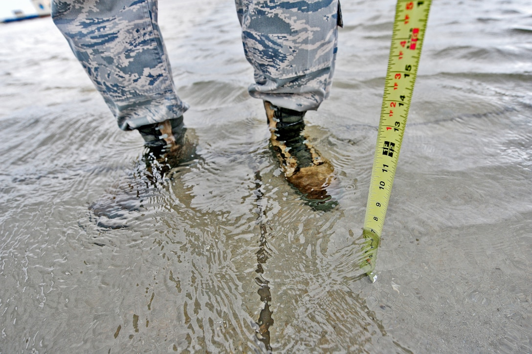 Staff Sgt. Timothy Cole, 509th Operations Support Squadron airfield management operations supervisor, measures the depth of rainwater during a during a daily safety inspection at Whiteman Air Force Base, Mo., May 31, 2013. Airfield managers must ensure safe flight conditions for any aircraft on the runway. (U.S. Air Force photo by Staff Sgt. Nick Wilson/Released)