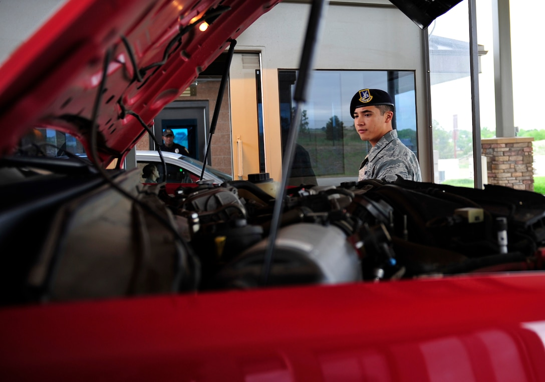 Senior Airman Michael Ngo, 460th Security Forces Squadron, searches a commercial vehicle June 5, 2013, at the Mississippi Gate on Buckley Air Force Base, Colo. In order for any commercial vehicle to gain access to a military installation, there must be a detailed vehicle search. Ngo's daily duties are to secure the gates, inspect commercial vehicles that enter the base, relay information from the driver such as license, registration and work orders, and also verify if individuals can gain access to the installation. (U.S. Air Force photo by Airman 1st Class Darryl Bolden Jr./Released)