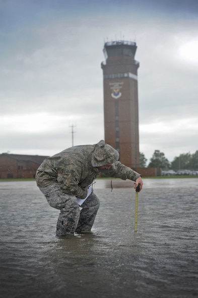 Staff Sgt. Timothy Cole, 509th Operations Support Squadron airfield management operations supervisor, measures the depth of rainwater on the flightline during a rainstorm at Whiteman Air Force Base, Mo., May 31, 2013. One of Coles' responsibilities is ensuring aircraft are able to safely taxi on the flightline to support contingency taskings and Air Force Global Strike Command operations. (U.S. Air Force photo by Staff Sgt. Nick Wilson/Released)