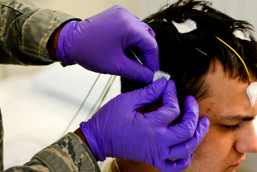U.S. Air Force Tech. Sgt. Valarie Platt, 633rd Medical Operations Squadron Neurology Clinic noncommissioned officer in charge, places an electrode on Airman 1st Class Christopher Howell, 633rd MDOS medical technician, prior to an electroencephalography (EEG) study at U.S. Air Force Hospital Langley at Langley Air Force Base, Va., May 4, 2013. The referral-based clinic sees between 120 and 140 patients monthly, focusing on individual, personalized care. (U.S. Air Force photo by Airman 1st Class R. Alex Durbin/Released)