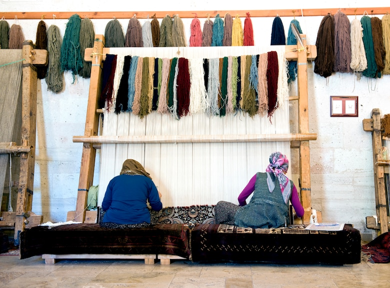 Turkish women tie knots on a weave to create a carpet May 5, 2013, in Goreme, Turkey. Turkish rugs are made in a wide variety of styles originating from the various regions in Anatolia. (U.S. Air Force photo by Senior Airman Daniel Phelps/Released)