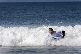Sgt. Dominic Theimann with Wounded Warrior Battalion rides a wave on his body board at the 6th annual 2013 USAA Commanding General's Surf Competition at the San Onofre Beach here, June 11. Competitors not only battled for CG's cup point for their units, but also for an automatic entry to the Red Bull Rivals competition July 13.