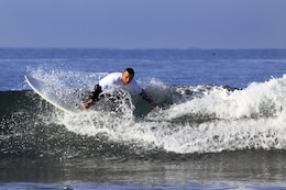 Col. Paul Miller with Headquarters and Support Battalion, Marine Corps Installations West, rides the very first set of waves during the 6th annual 2013 USAA Commanding General's Surf Competition at the San Onofre Beach here, June 11. More than 40 active duty Marines and sailors participated in the competition.