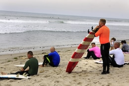 Competitors of the 6th annual 2013 USAA Commanding General's Surf Competition sit and wait to take their position in the waves of the San Onofre Beach here, June 11. The winners of the CG's surf competition were given automatic entry into the Red Bull Rivals competitions held July 13.