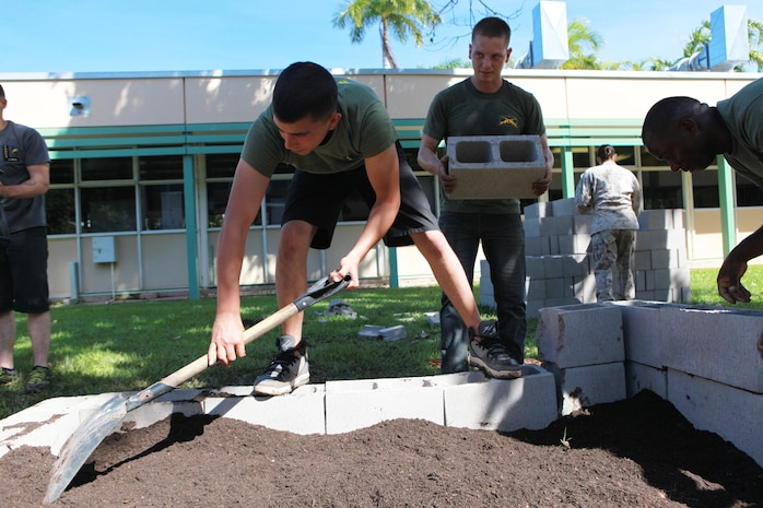 Lance Cpl. Isaac Hernandez, rifleman, 1st Platoon, Lima Company, 3rd Battalion, 3rd Marine Regiment, Marine Rotational Force - Darwin, spreads soil around the vegetable patch at the school, here, May 30. Marines with Marine Rotational Force - Darwin helped students with the foundation build a vegetable garden funded by the Consulate General of the United States, Melbourne. MRF-D Marines volunteer at the school every Thursday to help with projects like this and provide mentorship.