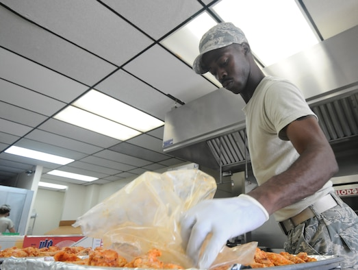 Staff Sgt. Wayne Collins, 36th Force Support Squadron food service supervisor, spreads chicken out evenly on a baking tray June 12, 2013, on Andersen Air Force Base, Guam. The Skyline Flight Kitchen prepares approximately 700 boxed lunches and 1,000 hot meals per week. (U.S. Air Force photo by Airman 1st Class Emily A. Bradley/Released)