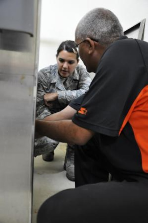 U.S. Air Force Staff Sgt. Rosalinda Alfaro, biomedical equipment technician from the 59th Medical Wing at Wilford Hall Ambulatory Surgical Center at Lackland Air Force Base, Texas, speaks with Roy Mencias, biomedical technician for the Northern Regional Hospital, regarding the hospital's steam sterilizer June 6, 2013 in Orange Walk, Belize. Alfaro is repairing medical sterilizers with various problems throughout Belize in the towns of Belmopan, Orange Walk and Dangriga. The effort is part of a training exercise called New Horizons. The training is designed to provide humanitarian assistance and medical care to people throughout Belize, while helping improve the skills of U.S. military medical forces. (U.S. Air Force photo by Capt. Holly Hess/Released)