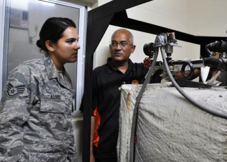 U.S. Air Force Staff Sgt. Rosalinda Alfaro, biomedical equipment technician from the 59th Medical Wing at Wilford Hall Ambulatory Surgical Center at Lackland Air Force Base, Texas, speaks with Roy Mencias, biomedical technician for the Northern Regional Hospital, regarding the hospital's steam sterilizer June 6, in Orange Walk, Belize. Alfaro is repairing medical sterilizers with various problems throughout Belize in the towns of Belmopan, Orange Walk and Dangriga. The effort is part of a training exercise called New Horizons. The training is designed to provide humanitarian assistance and medical care to people throughout Belize, while helping improve the skills of U.S. military medical forces. (U.S. Air Force photo by Capt. Holly Hess/Released)