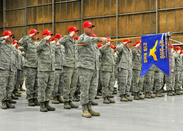 Members of the 219th RED HORSE Squadron salute during the posting of the colors during a change of command ceremony held at Malmstrom Air Force Base. (U.S. Air Force photo/Staff Sgt. John Turner)
