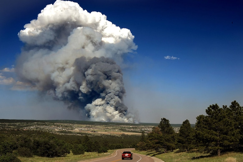 The Black Forest Fire smolders several miles east of the Air Force Academy in Colorado Springs, Colo., in this shot taken near the Cadet Chapel June 11, 2013. The fire burned between 7,500 and 8,000 acres the first day, as well as up to 100 homes. More than 5,000 people were evacuated from an additional 1,700 homes. (U.S. Air Force photo/Carol Lawrence)
