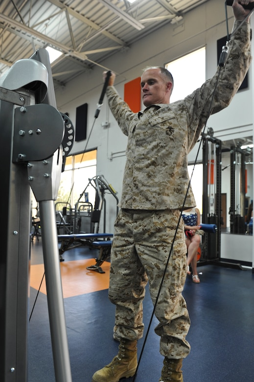 Marine Corps Maj. Brendan Egan, Company B, Intelligence Support Battalion executive officer, exercises on a pneumatic weight machine during a tour June 7, 2013, at the Denver Broncos training facility in Englewood, Colo. During the tour, the 12 Buckley Air Force Base, Colo. Marines tested the state-of-the-art exercise equipment used by the Broncos. They were given tips to improve overall health, physical fitness and exercise techniques. (U.S. Air Force photo by Airman 1st Class Riley Johnson/Released))