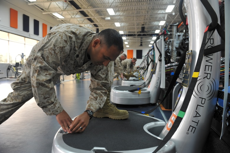 Marine Corps Sgt. Matthew Salazar, Company B, Intelligence Support Battalion, stretches on a Power Plate machine during a tour June 7, 2013, at the Denver Broncos training facility in Englewood, Colo.  The Broncos strength and training coaches shared fitness tips during the tour to 12 Buckley Air Force Base, Colo. Marines. (U.S. Air Force photo by Airman 1st Class Riley Johnson/Released)
