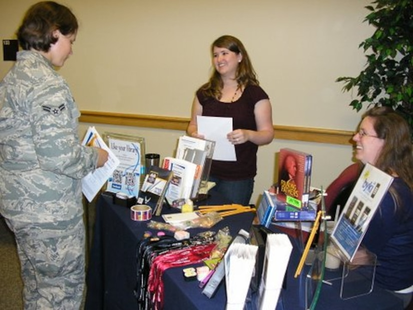 A Joint Base Charleston Airman speaks with representatives from one of the universities in attendance at an Education Fair May 30, 2013, at JB Charleston – Air Base, S.C. (U.S. Air Force photo/Courtesy photo)