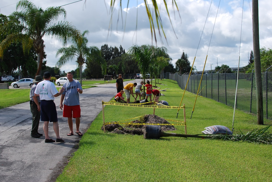 Steve Dunham, chief of the South Florida Operations Office in Clewiston (in white shirt) and park ranger Richard Bailey speak with army instructor Sergeant First Class Brian Lamberton as JROTC volunteers plant Royal Palms along the entrance to the Port Mayaca Lock & Dam.