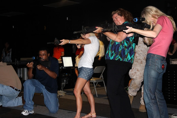 From left: Greg Taylor, Bridget Jukes and Susan Wood of Combat Support Systems are joined by Hallie Balkin, Office of the Counsel, as they take part in a May training exercise at Camp Upshur's Indoor Simulated Marksmanship Trainer.