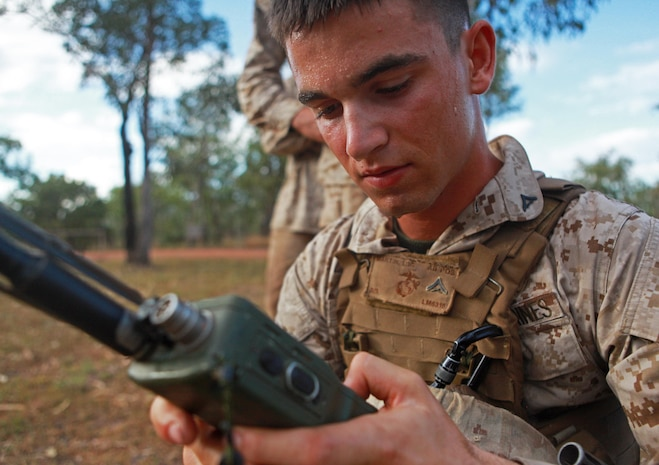 Lance Cpl. Luke Martin, 1st Platoon, Lima Company, 3rd Battalion, 3rd Marine Regiment, Marine Rotational Force - Darwin, calls for fire over the radio at the first station during a squad competition, here, May 23. MRF-D Marines ran approximately 4.5 miles, stopping only to complete different training exercises at four locations.