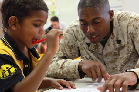 Sgt. Nathaniel Fowler, supply chief, Forward Coordination Element, Marine Rotational Force - Darwin, helps Alphonse, a student at Moulden Park Primary School, with a spelling exercise, here, May 15. Every Monday, Wednesday and Friday, Marines with Marine Rotational Force - Darwin volunteer at Moulden to support the local community.