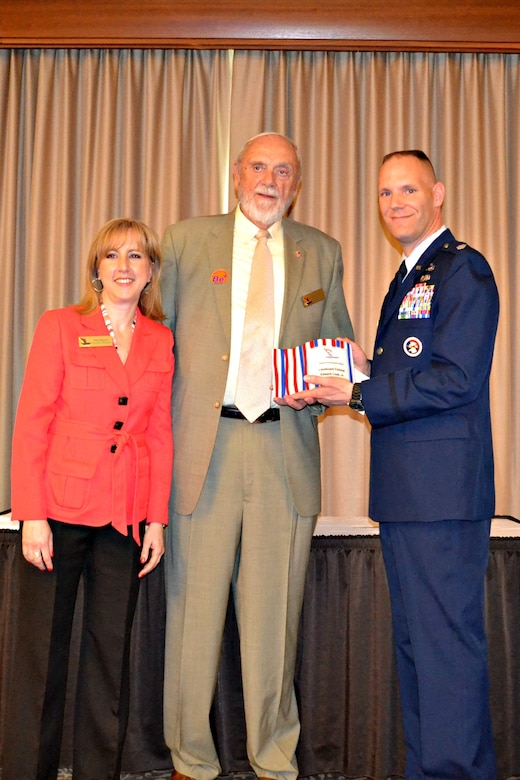 New York Air National Guard Lt. Col. Edward Cook (right) accepts the Leadership Greater Syracuse (LGS) Alumni Achievement Award from Ms. Pam Brunet, LGS Executive Director and Mr. William Sanford, LGS Chairman during a ceremony held on on April 24, 2013.  Lt. Col. Cook is the Logistrics Readiness Squadron Commander for the 174th Attack Wing, Hancock Field Air National Guard Base, Syracuse, New York, and a LGS 2010 graduate.  (photo by New York Air National Guard Lt. Col. Catherine Hutson/Released).