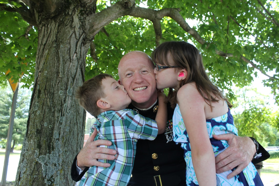 Maj. William Slack, fleet engagement team lead at Naval Supply Systems Command in Mechanicsville, Pa., receives a kiss from his daughter, Isabelle, 11, and son, Billy, 4, under a tree outside the Marine Corps Exchange aboard Marine Corps Base Quantico on June 6, 2013. Slack's family visited to congratulate him on graduating from Command and Staff College.