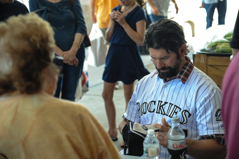 Todd Helton, Colorado Rockies first baseman, autographs a hat during a Rockies meet and greet June 14, 2013, at the commissary on Buckley Air Force Base, Colo. Team Buckley members had memorabilia signed by several Rockies players during the meet and greet, sponsored by Yancey's produce to thank service members and their families for their commitment, service and sacrifice. (U.S. Air Force photo by Staff Sgt. Christopher Gross/Released)