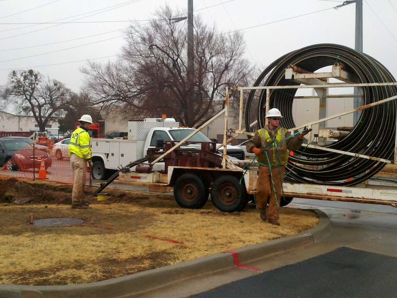 In an effort to make Tinker more energy efficient, workers install 4-inch gas lines along D Avenue. The base steam system will soon be decentralized and in its place, new energy-efficient equipment is being installed and individual gas lines are being run  to each building. (Air Force photo)