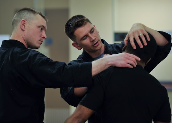 Tech. Sgt. Thomas Locke (center) shows Tech. Sgt. Ian Bobnes a pressure point on the neck of Staff Sgt. Ricardo Gray during a Combat Hapkido class at Osan Air Base, Republic of Korea, May 29, 2013. The structure and a lot of the techniques used in Combat Hapkido – like joint locks and the self-defense mind set – derive from traditional Hapkido, but Combat Hapkido is inclusive of many different martial arts. Locke is a Combat Hapkido instructor and a 694th Intelligence Support Squadron policy and evaluations inspector, Bobnes is a quality assurance technician with the 694th ISS, and Gray is a orthopedic surgical technician with the 51st Medical Operations Squadron. (U.S. Air Force photo/Senior Airman Siuta B. Ika)