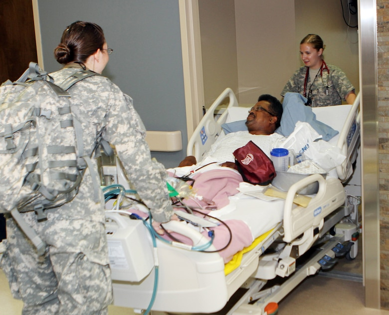 Nurses 1st Lt. Juliane Case, left and 1st Lt. Liana Gates wheel patient James Heckard into his room on the new fourth floor Inpatient Family Care Ward at the Evans Army Medical Center in Fort Carson, Colo.
