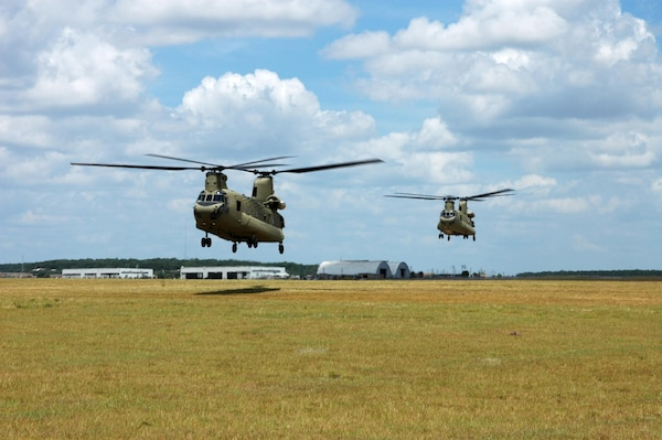"Two CH-47F Chinook helicopters from the 2nd ""Lobo"" Battalion, 227th Aviation Regiment, 1st Air Cavalry ""Warrior"" Brigade, 1st Cavalry Division, hover in a holding pattern at Hood Army Air Field, Fort Hood, Texas, July 10. Two similar Chinooks recently deployed in support of U.S. Northern Command, which is supporting federal, state and local response efforts in Texas."