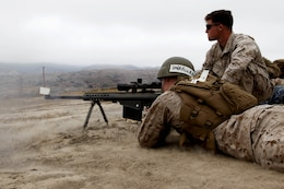 Midshipman 3rd Class Ronald Harrell fires a .50-caliber long-range sniper rifle with help from scout sniper Lance Cpl. John Lemar during Marine Week of Career Orientation and Training for Midshipmen-West 2013 here June 12. Future officers from across the U.S. participated in the four-weeks of training designed to introduce them to career opportunities.