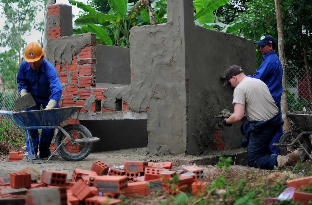 Construction workers with Vietnam People's Army and a U.S. Army Soldier build an incinerator that will be used to burn medical waste, as part of the Engineering Civil Action Programs for Operation Pacific Angel 13-3 in Dong Hoi, Quang Binh Province, Vietnam, June 12, 2013. U.S. and Vietnam military members joined together to complete construction projects on one medical clinic and two schools in Vietnam. Operation PACANGEL is a joint and combined humanitarian assistance exercise held in various countries several times a year and includes medical, dental, optometry, engineering programs and a variety of subject-matter expert exchanges. (U.S. Air Force photo by Staff Sgt. Sara Csurilla)
