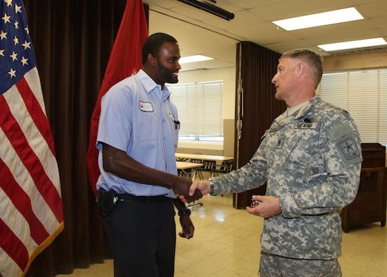 (l to r) Daaniyal Mcgill, Distribution and Electrical Section, Maintenance Branch, receives a coin for his outstanding service from Sgt. Maj. of the Army Raymond F. Chandler III. Chandler visited the Washington Aqueduct to learn more about the Corps unique and diverse mission, June 5.